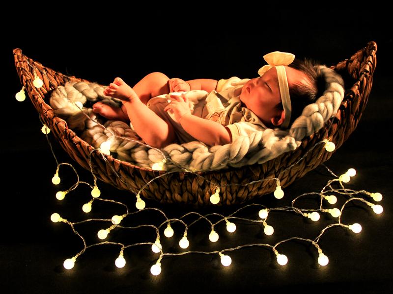 newborn baby in twinkle lights