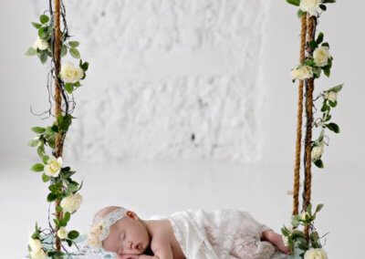 artistic newborn baby girl on the swing